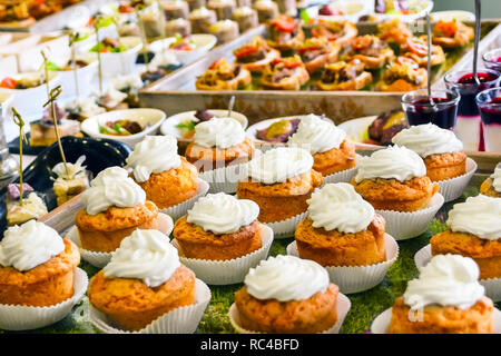 Catering Services Concept: Vanilla Cupcakes Topped With White Cream, Various Snacks Served at a Business Event, Hotel, Birthday or Wedding Celebration - Stock Photo