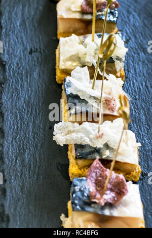 Catering Services Supply: Knots of Natural Bamboo Skewers in Fish Canapes on Black Slate Serving Stone Served at a Business Event, Hotel, Birthday or  - Stock Photo