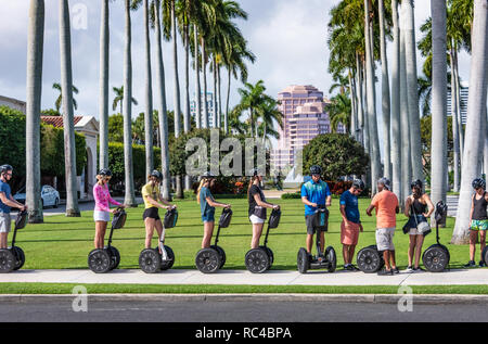 Segway tour group at the Society of the Four Arts in Palm Beach, with downtown West Palm Beach, Florida in the background. (USA) - Stock Photo