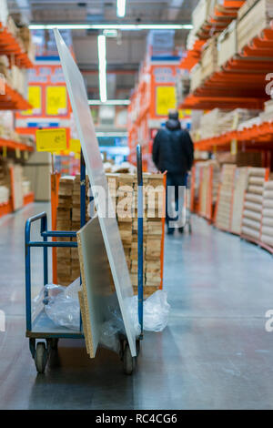 construction cart in the building store. Carts loaded with boards. shop of building materials. Racks with boards, wood and building material. loaded c - Stock Photo