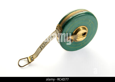 10 meter vintage measuring ribbon or tape-measure in round green body with yellow metal handle. Viewed from high angle in close-up, isolated on white  - Stock Photo
