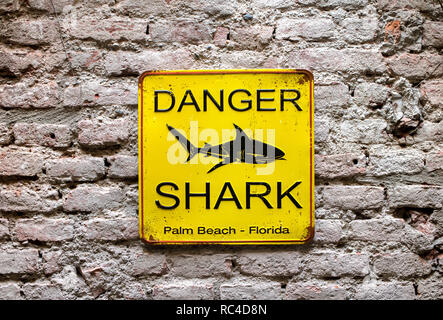 Yellow square metal Danger Shark sign with black shark silhouette image viewed in close-up and full frame on old brick wall. Palm Beach, Florida - Stock Photo
