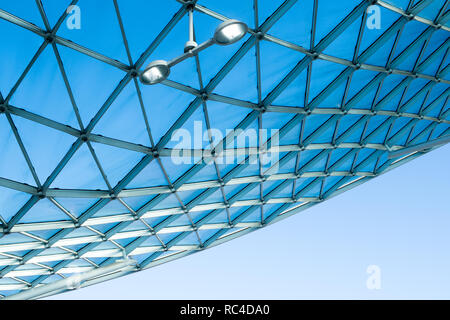 Modern architecture glass roof with curved design of steel structure. Low angle view with blue sky, indoor lighting and white wall of the building - Stock Photo