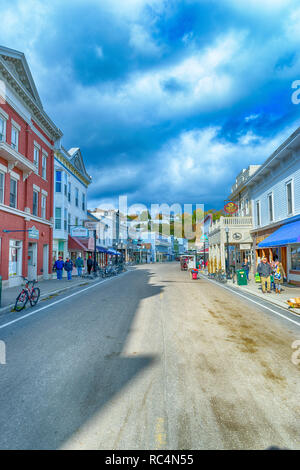 Main Street Mackinac Island, Michigan / United States - October 16, 2018:  Tourists enjoying the island on a windy day in October. - Stock Photo