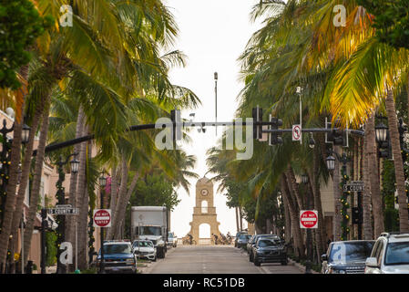 Palm tree lined Worth Avenue and oceanfront Clock Tower with early morning cyclists in Palm Beach, Florida. (USA) - Stock Photo