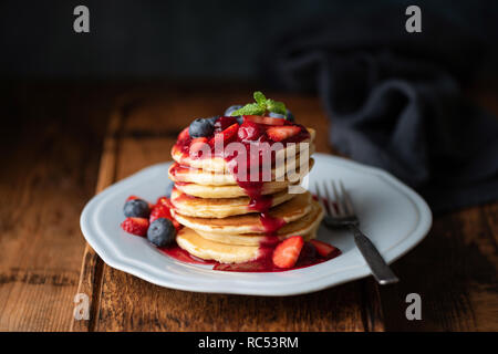 Tasty Pancakes With Berry Sauce On Wooden Table. Closeup view. Low Key Food Photography - Stock Photo