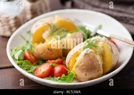 Baked stuffed potatoes with cheese, sour cream and dill on a plate. Healthy tasty dinner - Stock Photo