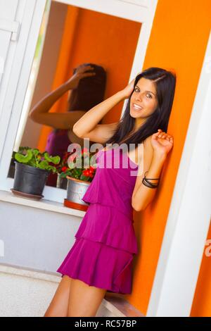 Teen girl and her glass reflection looking at camera smiling - Stock Photo