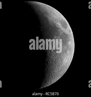 Big waxing crescent Moon with high details on his grey surface, all in a black background, taken with large newtonian reflector telescope. - Stock Photo