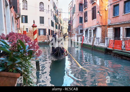 Venice, Italy - February 10, 2018: Gondolier rides gondola through the narrow canal between colorful historic houses on a sunny winter day - Stock Photo