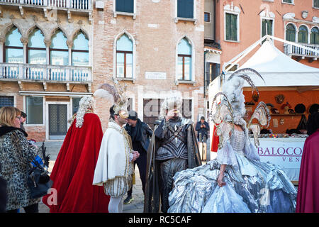 Venice, Italy - February 10, 2018: People in gold masks and white and silver costumes on the street during the Carnival - Stock Photo