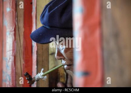 GUIZHOU PROVINCE, CHINA – CIRCA DECEMBER 2018: An old ethnic minority man stood in the doorway and puffed away at his pipe. - Stock Photo