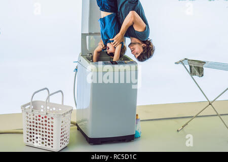 Father tries to wash his son in a washing machine standing upside down with his feet - Stock Photo