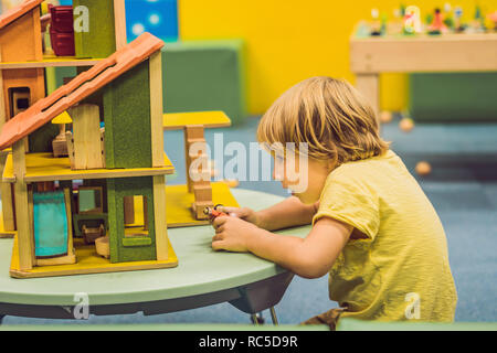 Boy playing with wooden house in kindergarten - Stock Photo