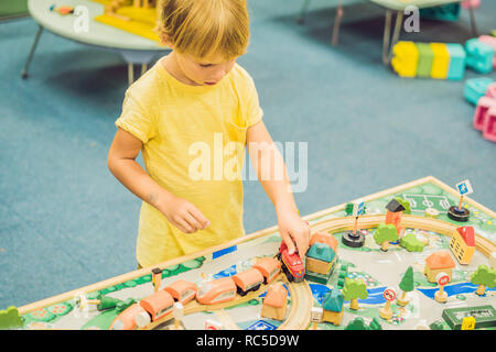 Children play with wooden toy, build toy railroad at home or daycare. Toddler boy play with crane, train and cars. Educational toys for preschool and kindergarten child. Cushioned furniture, chair bag - Stock Photo