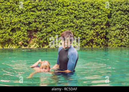 Male instructor swimming for children teaches a happy boy to swim in the pool - Stock Photo