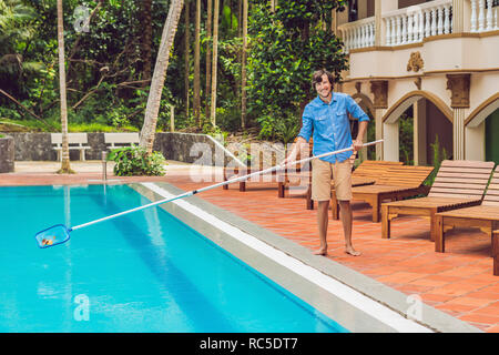 Cleaner of the swimming pool . Man in a blue shirt with cleaning equipment for swimming pools, sunny - Stock Photo
