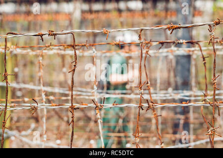 Barbed wire, a fence in prison and the silhouette of a prison guard on the background - Stock Photo