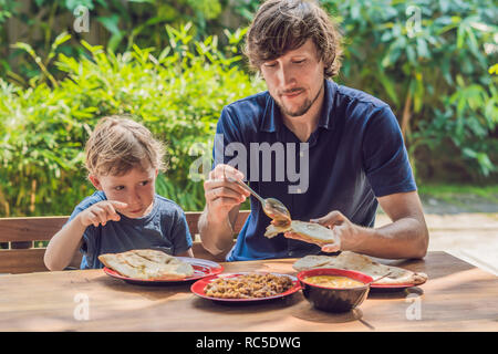 Father and son try Indian food in a cafe on the street - Stock Photo