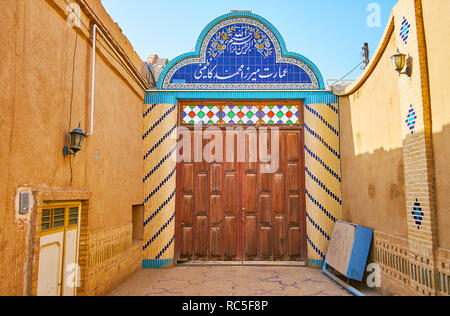 YAZD, IRAN, OCTOBER 18, 2017: The scenic gate, decorated with tiled patterns and the massive wooden door of historic gate, occupied by Yazd Bar Associ - Stock Photo