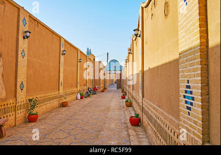 YAZD, IRAN, OCTOBER 18, 2017: The long narrow inner court of historic mansion of Yazd Bar Association with adobe walls, decorated with brickwork and g - Stock Photo