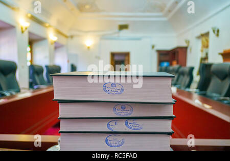 YAZD, IRAN, OCTOBER 18, 2017: The stack of books of law on the table in conference hall of Yazd Bar Association, on October 18 in Yazd. - Stock Photo