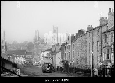 St Mary's Cathedral Church, Minster Yard, Lincoln, Lincolnshire, c1955-c1980. General view of Lincoln looking along Melville Street towards the Green Dragon Public House, with St Swithin's Church in the midground and St Mary's Cathedral Church in the background. The image shows a general view of Lincoln north of the River Witham, and shows three listed buildings amongst the rooftops. On the left side of the image, past the entrance to a road bridge is the Green Dragon public house, a timber-framed building with arch braces and a jettied top floor with four gables, three of which can be seen. P - Stock Photo