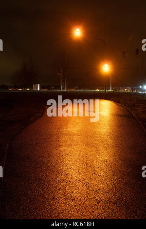 Orange traffic light at night with red reflection on wet asphalt. - Stock Photo