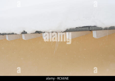 Snow on roof after two days of snowfalls, Snow cyclone in Europe. House roof covered with snow - Stock Photo