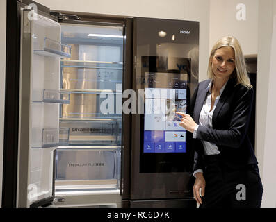 14 January 2019, North Rhine-Westphalia, Köln: A model operates a programmable refrigerator on the display (manufacturer: Haier). The International Furniture Fair imm cologne will take place from 14 - 20 January 2019. Photo: Oliver Berg/dpa - Stock Photo
