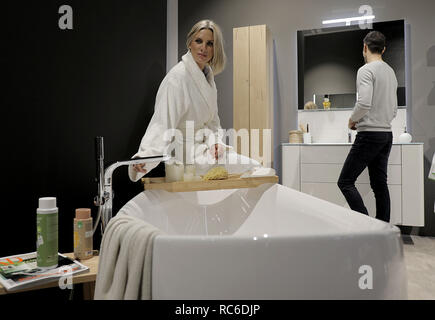 14 January 2019, North Rhine-Westphalia, Köln: A model sits at a bathtub in a bathroom (manufacturer: Hülsta). The International Furniture Fair imm cologne will take place from 14 - 20 January 2019. Photo: Oliver Berg/dpa - Stock Photo