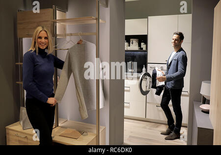 14 January 2019, North Rhine-Westphalia, Köln: Models stand in a kitchen with utility room (manufacturer: Nobilia). The International Furniture Fair imm cologne will take place from 14 - 20 January 2019. Photo: Oliver Berg/dpa - Stock Photo