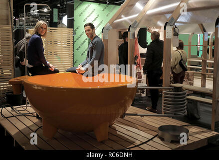 14 January 2019, North Rhine-Westphalia, Köln: Models sit at a heated bathtub for the garden (manufacturer: Weltevree, NL). The International Furniture Fair imm cologne will take place from 14 - 20 January 2019. Photo: Oliver Berg/dpa - Stock Photo