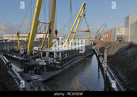 14 January 2019, North Rhine-Westphalia, Köln: A ship hangs from a crane in Niehl harbour. The party ship sank at Christmas in a Cologne harbour and was lifted out of the water by a floating crane. Photo: Oliver Berg/dpa - Stock Photo