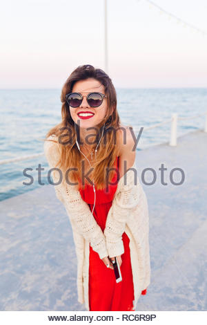 Close-up portrait of a beautiful girl in red dress and white jacket on a pier, smiling and listening to music on earphones on a smartphone. She wears dark sunglasses. - Stock Photo