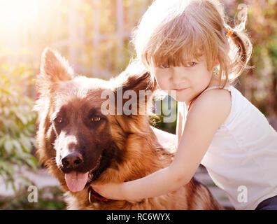 Pretty little girl, hugging her fluffy friend, german shepherd dog. - Stock Photo