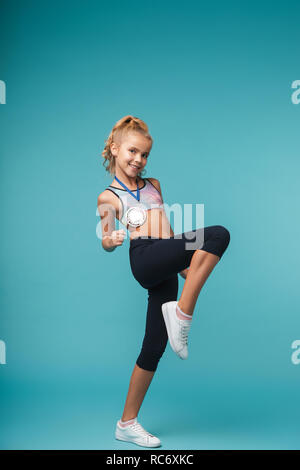 Image of a cute little girl child with a medal posing isolated over blue wall showing winner gesture. - Stock Photo