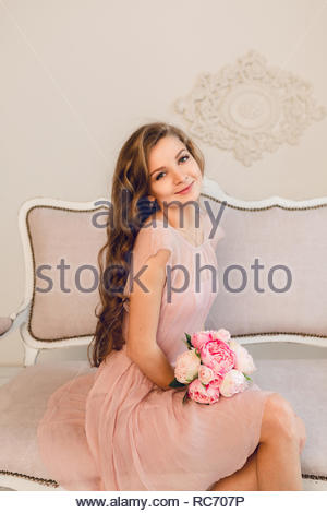 Charming blond girl sitting on a sofa. She has long curly hair and holds a bouqet of peonies in her hands. She wears peach color light dress. - Stock Photo