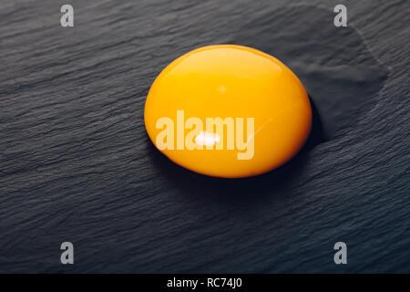 chicken egg yolk closeup on black stone background