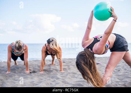 Group of three beautiful young girls doing exercises outdoor pilates and push up workout together in friendship having fun for healthy lifestyle enjoy - Stock Photo
