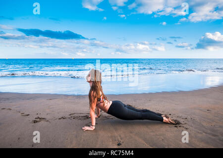 Cobra snake pilates yoga position outdoor for caucasian young woman doing it on the shore on the sand at the beach with blue ocean and sky in backgrou - Stock Photo