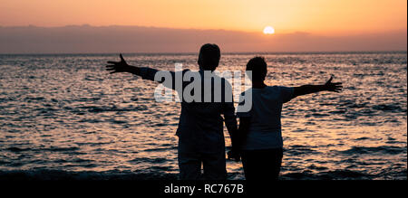 Valentine's day concept with couple in silhouette enjoying red coloured beautiful sunset together opening arms and having joy with nature outdoor leis - Stock Photo