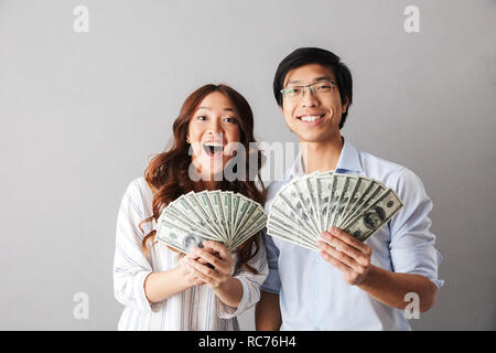 Happy asian business couple standing isolated over gray background, holding money banknotes - Stock Photo