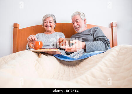 couple of adult senior at home doing breakfast together in the bed at morning - indoor activity for married people - ground view and man and woman hav