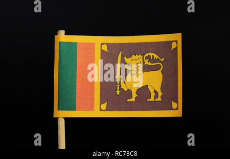 The official and national flag of Sri Lanka  on toothpick on black background. A yellow field with two panels: the smaller hoist-side panel has only t - Stock Photo