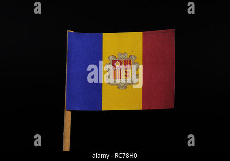 A official and national flag of the Principality of Andorra on toothpick on black background. A vertical tricolour of blue, yellow and red with the Na - Stock Photo