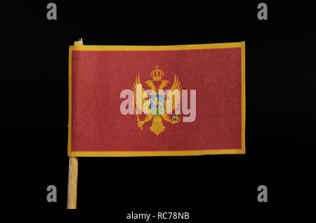 A official and national flag of Montenegro on toothpick on black background. A red field surrounded by a golden border; charged with the Coat of Arms  - Stock Photo