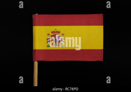 A official and national flag of Spain on toothpick on black background. A horizontal tricolour of red, yellow  and red with Spanish coat of arms. - Stock Photo