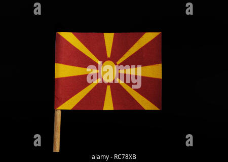 A unique and very original, national flag of the Republic of Macedonia on toothpick on black background. Stylised yellow sun on red field, with eight  - Stock Photo