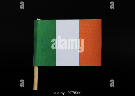 A tricolour flag of Ireland on toothpick on black background. A vertical tricolour of green, white and orange. - Stock Photo